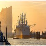 Hamburg, Landungsbrücken. Elbphilharmonie, Cap San Diego und HMS Sutherland im Sonnenaufgang.